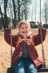Little smilling girl swinging in a park on sunny spring day