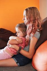 Teenage girl and her little sister watching TV