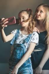 Young women taking selfie, using smartphone camera