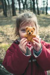 Little girl playing with her little teddy bear toy in a park