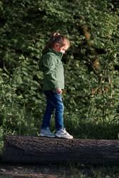 Little girl walking on stump in forest
