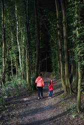 Mother with her little daughter walking through the forest