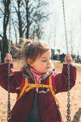 Little cute girl swinging in a park on sunny spring day