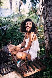 african young woman sitting on swing in garden