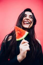 Junge glückliche Frauen, die Wassermelone genießen