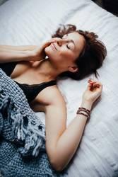 Junge lächelnde Frauen, die in bequemes Bett legen