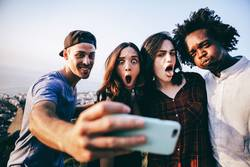 Group of mixed race adults taking selfie with smart phone