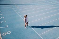 Junger weiblicher Athlet auf blauer Laufbahn
