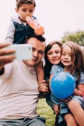 Glückliche kaukasische Familie, die zusammen selfie mit Telefon nimmt