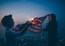 African man and Girl celebrating with USA flag and sparkler