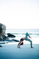 Junge Frauen, die morgens Yogaaufstellung auf Strand tun