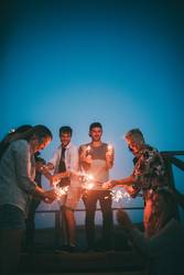 mixed group of young adults having fun at summer night outside