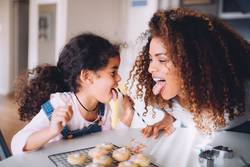 mother and daughter having fun eating cookies together