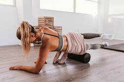 Woman using foam roller in the gym