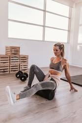 young woman foam rolling after exercise in gym