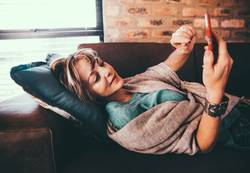 Modern mature woman laying on couch browsing internet