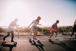 Group of hipster friends longboarding on the road in summer