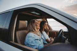 two attractive women driving truck at beach