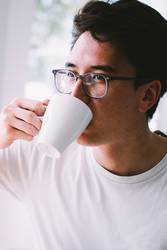 Asian young adult drinking cup of fresh coffee in the morning