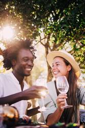 Cute mixed race couple enjoying wine together on date