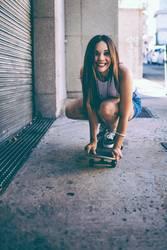Happy female riding skate board in street