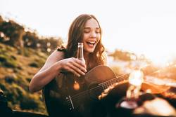 Young adult woman enjoying beer and playing guitar