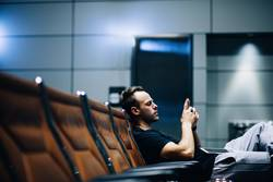 Young adult man waiting in airport lounge using smart phone