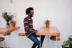 Young happy afro american man sitting in cafe
