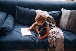 young caucasian little boy playing with tablet on couch