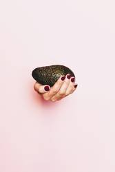 Hand of a woman holding an avocado