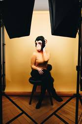 Woman with monkey mask posing in photo studio