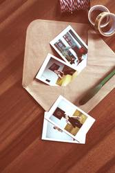 Instant pictures and envelope on table (01)