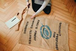 Upcycling - woman making garments from coffee sack