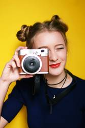 Young woman taking pictures with an instant camera
