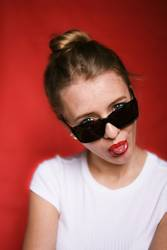 Young woman with sunglasses stretching out tongue