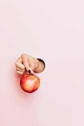 Hand of a woman holding an apple