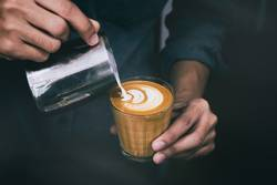 Barista pouring hot milk prepare latte art on cup of coffee