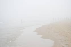 Menschen am Meer im Nebel.