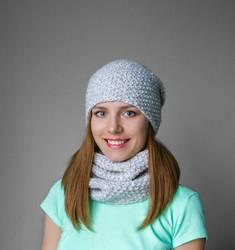 Lächelndes junges Mädchen in der Winterkappe und -schal