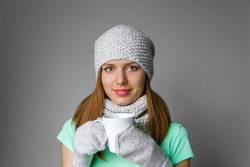 Lächelndes junges Mädchen in der Winterkappe, -schal und -handschuhe mit Becher