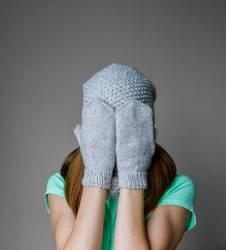 Lächelndes junges Mädchen in der Winterkappe, -schal und -handschuhen