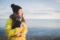 Woman with her little dog on the beach in winter