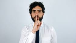 Man with shirt and tie asking for silence