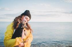 Woman with her little dog on the beach