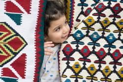 Little girl close up portrait between kilims patterns