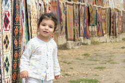 Little girl portrait in front of colorful kilims