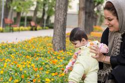 Muslim mother holding Little baby inside spring flowers at park
