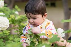 Little baby girl in colorful cloth inside spring flowers at park