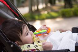 Little baby with yellow dummy at mouth resting at baby carriage