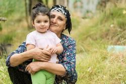 Senor grandmother embraced her little grandchild at field